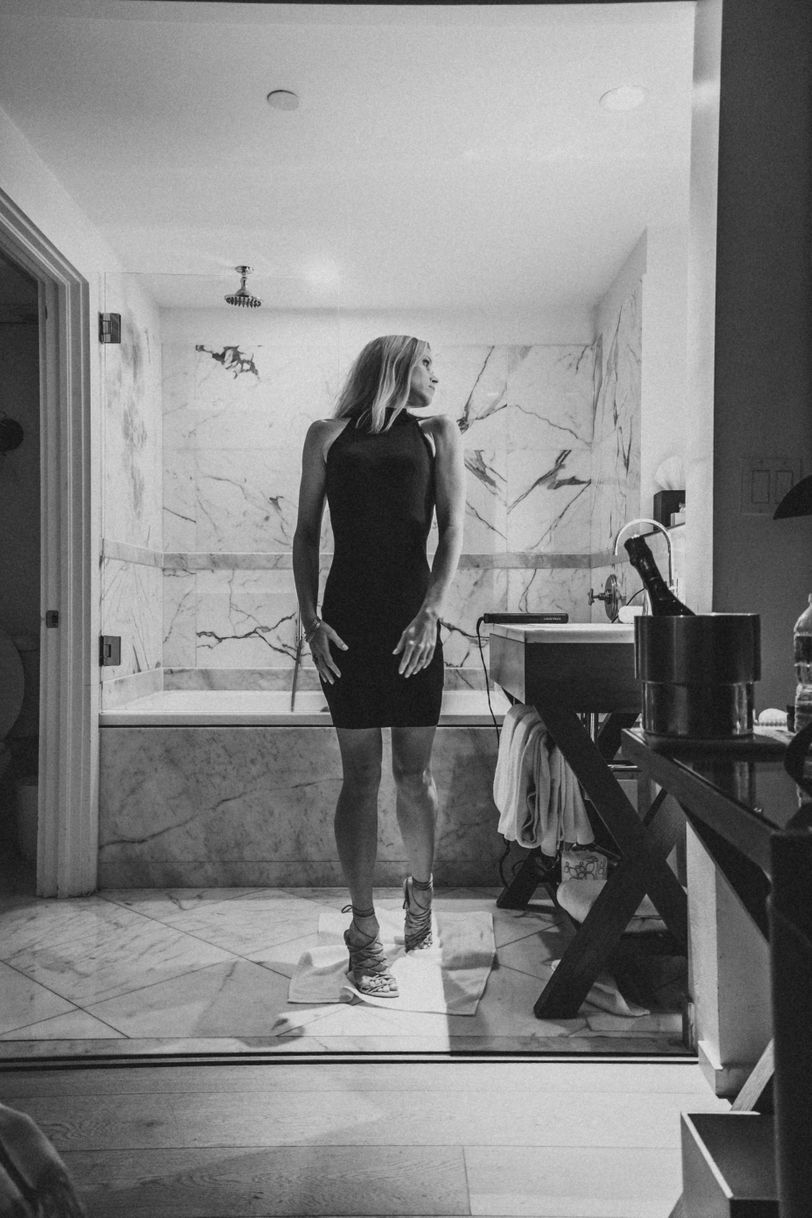 Getting ready at Hotel Victor, wearing a mini dress and strappy heels.